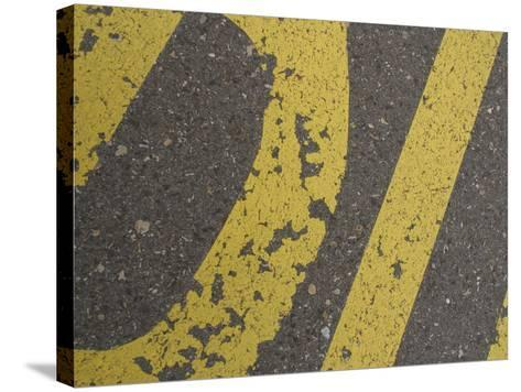 Close-up of Yellow Letters Painted on Gray Asphalt--Stretched Canvas Print