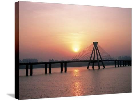 Bright Sunset with Suspension Bridge Over Water--Stretched Canvas Print
