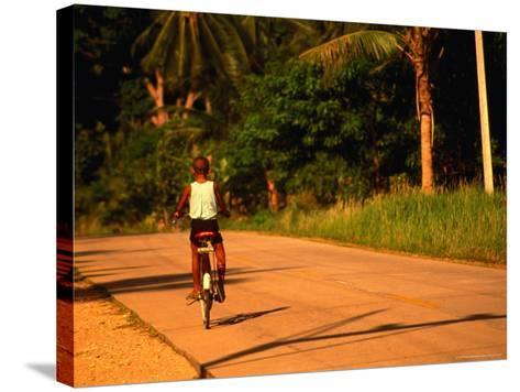 Boy Riding Bike on Dirt Road, Ko Samui, Surat Thani, Thailand-Dallas Stribley-Stretched Canvas Print