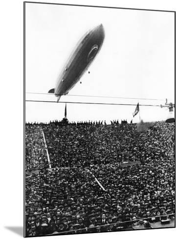 Graf Zeppelin Passing Low over Wembley Stadium During FA Cup Final Where Arsenal Beat Huddersfield--Mounted Photographic Print