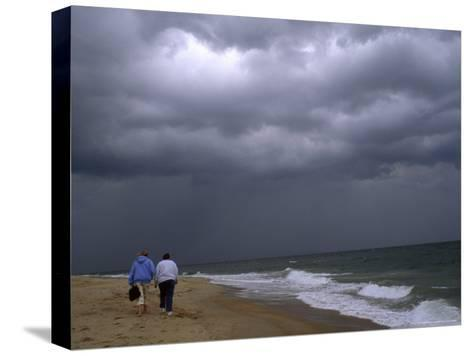 Daughter and Mother Walk Along a Beach, Storm Clouds Darken the Sky-Brian Gordon Green-Stretched Canvas Print