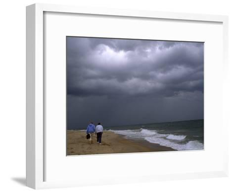 Daughter and Mother Walk Along a Beach, Storm Clouds Darken the Sky-Brian Gordon Green-Framed Art Print