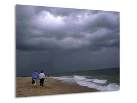 Daughter and Mother Walk Along a Beach, Storm Clouds Darken the Sky-Brian Gordon Green-Metal Print