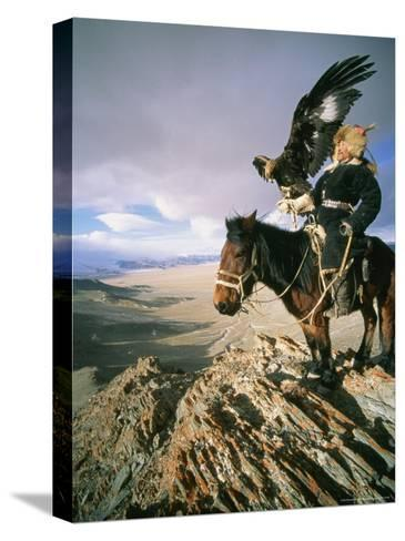 Hunter on Horseback Atop a Hill Holding a Golden Eagle in Mongolia-David Edwards-Stretched Canvas Print