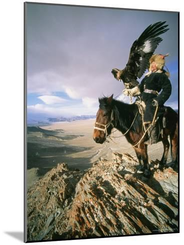 Hunter on Horseback Atop a Hill Holding a Golden Eagle in Mongolia-David Edwards-Mounted Photographic Print