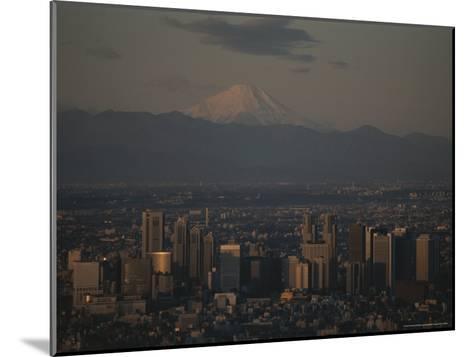 Mt. Fuji Looms in the Distance Over Tokyo's Skycrapers-Karen Kasmauski-Mounted Photographic Print
