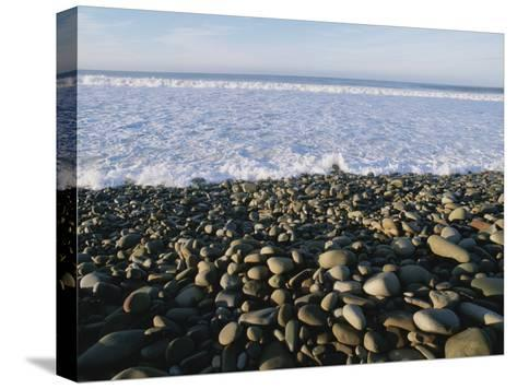Whitewater From Crashing Waves Washes onto a Pebble Beach-Rich Reid-Stretched Canvas Print