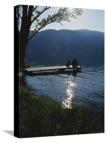 Man and His Dog on a Lake Skaha Dock-Mark Cosslett-Stretched Canvas Print