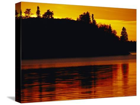 The Setting Sun Casts an Orange Glow Over Manitoba's White Lake-Raymond Gehman-Stretched Canvas Print