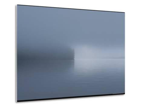 Thick Fog Hangs Over Eerily Calm Water Where a Point of Land Juts Out-Bill Curtsinger-Metal Print