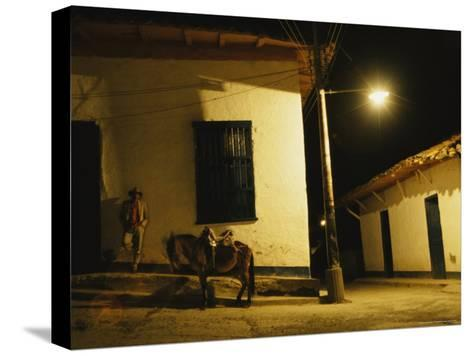 Man Rests Against a Wall Near His Donkey Under a Streetlight-David Evans-Stretched Canvas Print