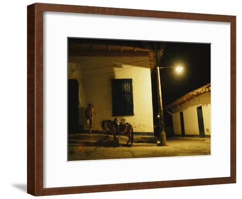 Man Rests Against a Wall Near His Donkey Under a Streetlight-David Evans-Framed Art Print