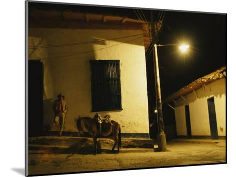 Man Rests Against a Wall Near His Donkey Under a Streetlight-David Evans-Mounted Photographic Print