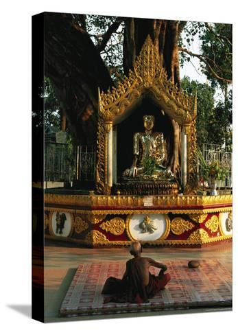 Buddhist Monk Meditating Near Altar with Buddha Statue and Gilt-Steve Winter-Stretched Canvas Print
