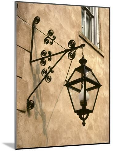 Iron Street Lamp Hangs From a Historic Building-Rex Stucky-Mounted Photographic Print