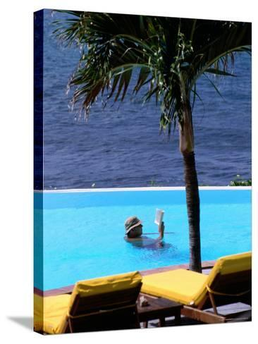 Tourist Reading Book in Swimming Pool with Ocean in Background, Palm Tree in Foreground-Pascale Beroujon-Stretched Canvas Print