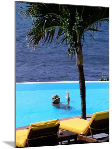 Tourist Reading Book in Swimming Pool with Ocean in Background, Palm Tree in Foreground-Pascale Beroujon-Mounted Photographic Print