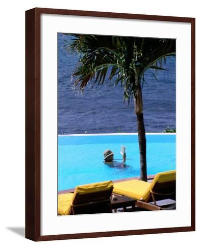 Tourist Reading Book in Swimming Pool with Ocean in Background, Palm Tree in Foreground-Pascale Beroujon-Framed Art Print