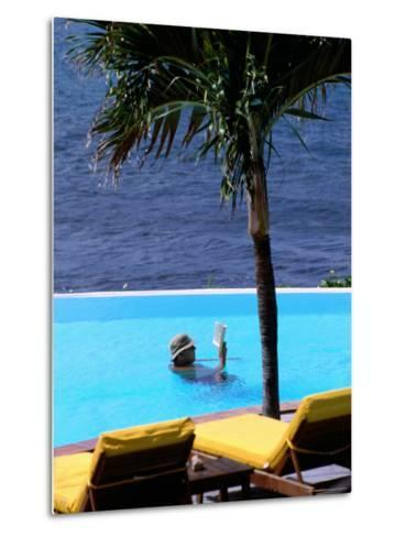 Tourist Reading Book in Swimming Pool with Ocean in Background, Palm Tree in Foreground-Pascale Beroujon-Metal Print