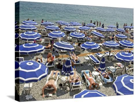 Blue Umbrellas and People Crowd Beach-Russell Mountford-Stretched Canvas Print