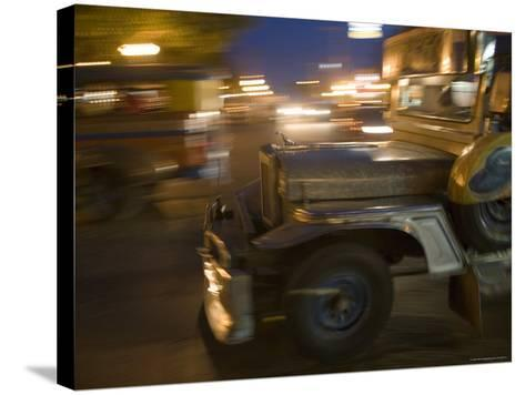 Jeepney Speeds Through Night in Malate-Greg Elms-Stretched Canvas Print