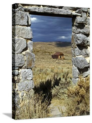 1880's Deserted Home Through Stone Warehouse Door Frame, Bodie State Historic Park-Emily Riddell-Stretched Canvas Print