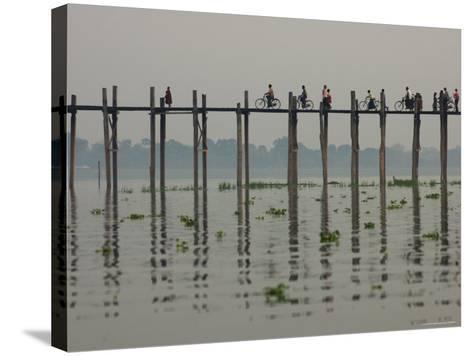 People Ride their Bicycles Along U Bein's Bridge That Runs Down the Taungthaman Lake-David Greedy-Stretched Canvas Print