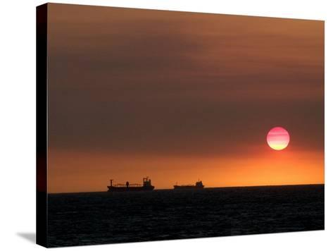 Cargo Ships Silhouetted on Horizon at Sunset, Cottesloe Beach-Orien Harvey-Stretched Canvas Print