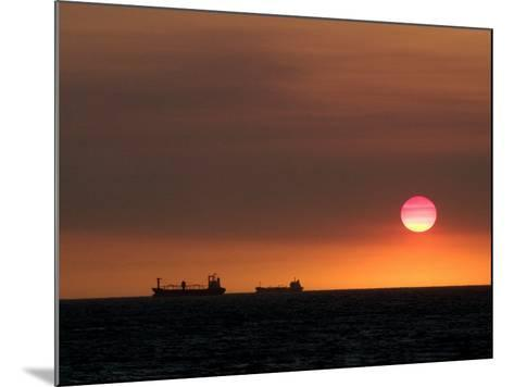 Cargo Ships Silhouetted on Horizon at Sunset, Cottesloe Beach-Orien Harvey-Mounted Photographic Print