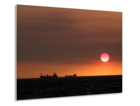 Cargo Ships Silhouetted on Horizon at Sunset, Cottesloe Beach-Orien Harvey-Metal Print