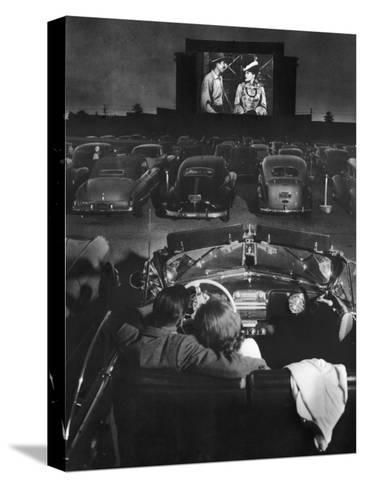 Young Couple Snuggling in Convertible as They Watch Large Screen Action at a Drive-In Movie Theater-J^ R^ Eyerman-Stretched Canvas Print