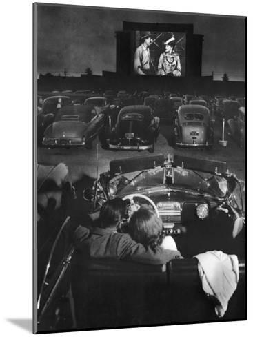 Young Couple Snuggling in Convertible as They Watch Large Screen Action at a Drive-In Movie Theater-J^ R^ Eyerman-Mounted Photographic Print