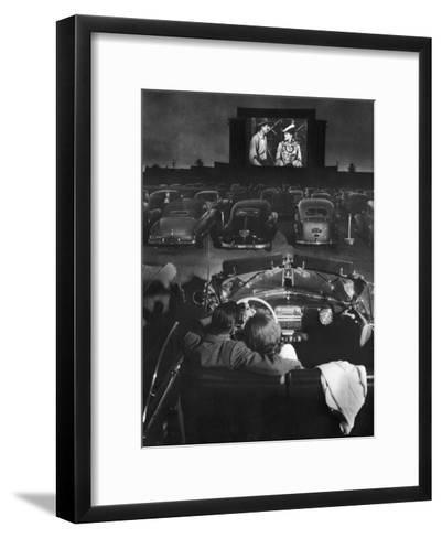 Young Couple Snuggling in Convertible as They Watch Large Screen Action at a Drive-In Movie Theater-J^ R^ Eyerman-Framed Art Print