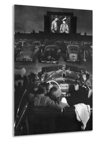 Young Couple Snuggling in Convertible as They Watch Large Screen Action at a Drive-In Movie Theater-J^ R^ Eyerman-Metal Print