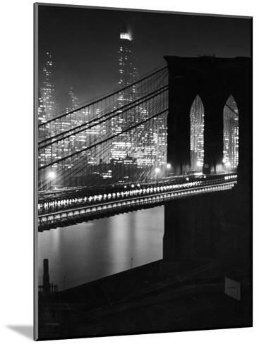 Glittering Night View of the Brooklyn Bridge Spanning the Glassy Waters of the East River-Andreas Feininger-Mounted Photographic Print