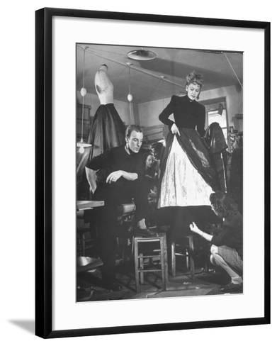 Jacques Fath Watching as the Tailor Hymns the Loose Ends at the Bottom of the Dress-Nina Leen-Framed Art Print