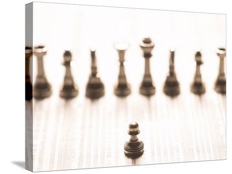 Selective Focus of Silver Pawn on Newspaper Stock Market Report with Line of Chess Pieces--Stretched Canvas Print