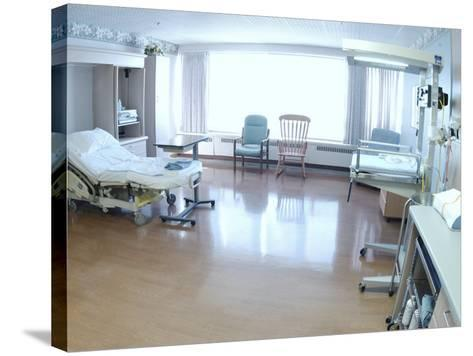 Hospital Bed, Chairs, and Medical Equipment Arranged in Empty Hospital Room--Stretched Canvas Print