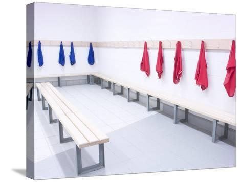 Blue and Red Shirts Hanging from Hooks in School Gym Change Room--Stretched Canvas Print
