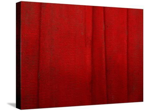 Bright Red Fire Hose Made of Tightly Woven Fabric and Folded into Layers--Stretched Canvas Print