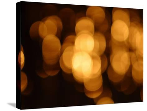 Blurry Orange Lights Illuminating Against a Black Background--Stretched Canvas Print