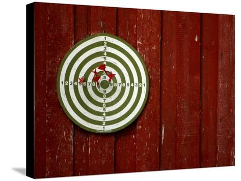 Old Dart Board Game Hanging on a Weathered Red Wall--Stretched Canvas Print