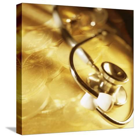 Stethoscope Lying over Gold Coins--Stretched Canvas Print