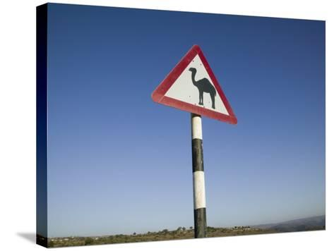 Oman, Dhofar Region, Salalah, Camel Crossing Sign in the Dhofar Mountains-Walter Bibikow-Stretched Canvas Print