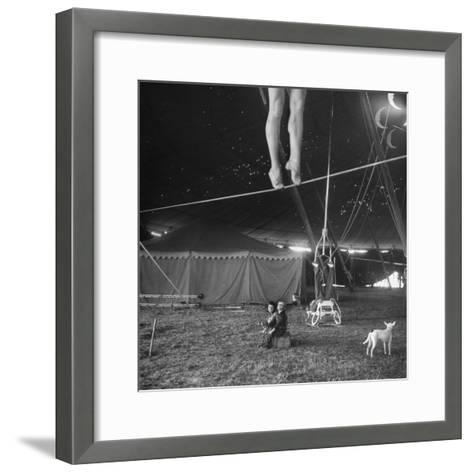 Two Small Children Watching Circus Performer Practicing on Tightrope, Her Legs Only Visible-Nina Leen-Framed Art Print
