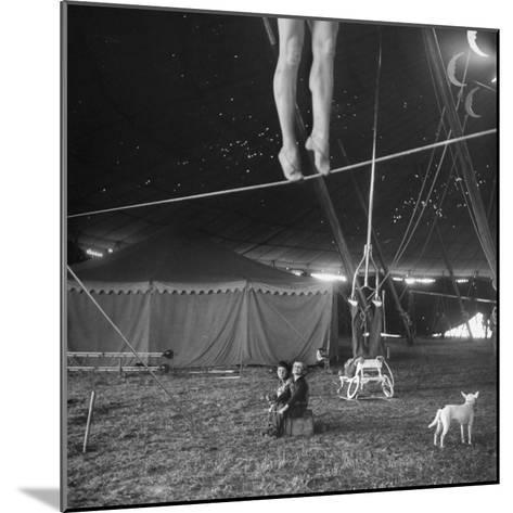 Two Small Children Watching Circus Performer Practicing on Tightrope, Her Legs Only Visible-Nina Leen-Mounted Photographic Print