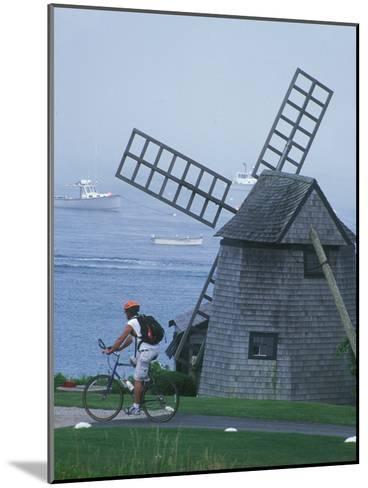 Bicyclist Rides Past a Windmill on a Cape Cod Shore, Chatham, Massachusetts-Darlyne A^ Murawski-Mounted Photographic Print
