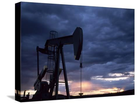 Oil Rig Silhouetted at Sunset, Adobe Town, Wyoming-Joel Sartore-Stretched Canvas Print