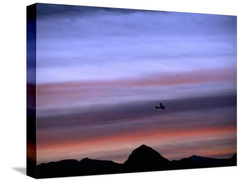 Aircraft and Mountains Silhouetted Against a Dramatic Sky at Dusk, Wyoming-Joel Sartore-Stretched Canvas Print