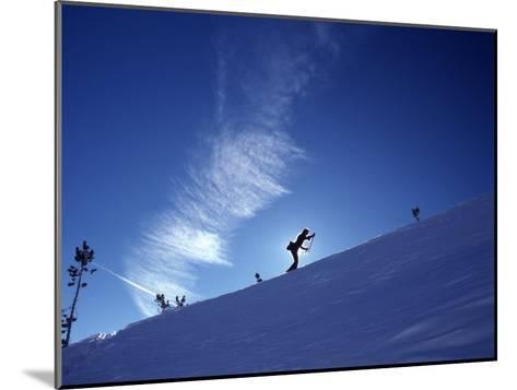 Silhouette of a Woman Cross Country Skiing Up a Snowy Slope, Mount Rose, Nevada, United States-Kate Thompson-Mounted Photographic Print